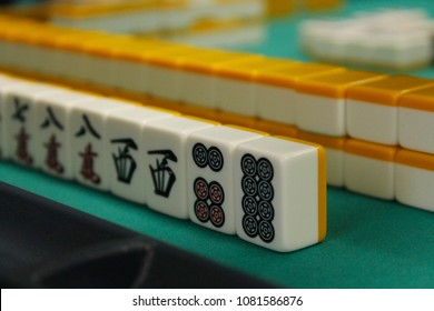 The bones (tiles) for the mahjong lie on the green table, the back and side plan is blurred. Table traditional game of Asia.