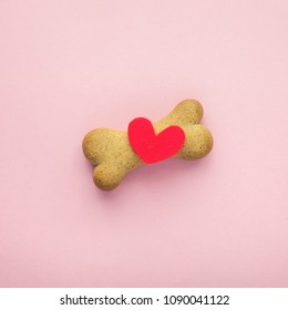 bone-shaped biscuit for dog and red heart on pink background, concept pet care