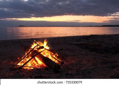 Bonfire burning on the riverbank  on the sunset, Ob river, Siberia, Russia
