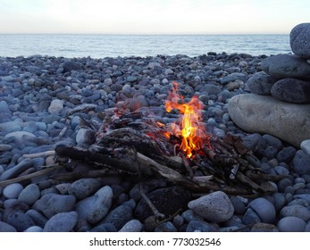 Bonfire or campfire in stone place on pebbles beach on the background of sea and evening sky. Bonfire in a campfire on pebble coast. Bright bonfire burning on the beach at sunset.