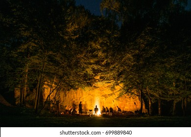 Bonfire in the dark woods next to rock