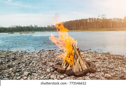 A bonfire in the form of a tent that burns on the river bank at sunset, the river, Siberia, Russia. Bonfire on the beach at sunset. Fire on the beach. Lonely fire on the seashore in autumn