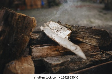 Bonfire in the grill. Punctured firewood lies in a fire in a metal forged brazier. Fire and smoke are visible.