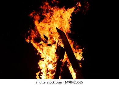 bonfire night campfire wood burning flame on dark black , selective focus
