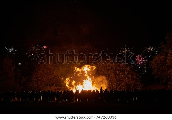 Bonfire night - A crowd of people watch a bonfire with fireworks in the sky in the background.