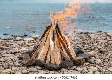 Bonfire on the beach at sunset. Bonfire on the sandy beach. Fire on the beach. Lonely fire on the seashore in autumn