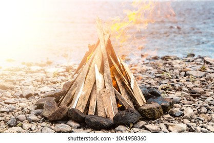 A bonfire on the beach at sunset. A bonfire on a stone beach. Fire on the beach - selective focus, copy space. Lonely fire on the seashore in autumn