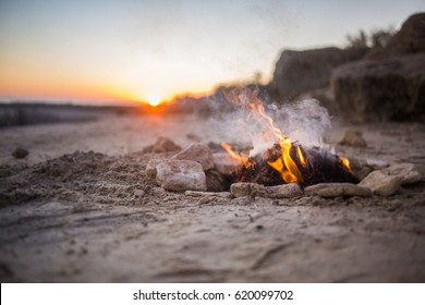 Bonfire on sand beach. Orange sunset.