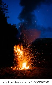 A bonfire raging against a dark blue night sky.  Embers and sparks flying off in all directions.  High red hot flames.