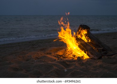 Bonfire in the sand against the background of the waves and the dark blue sky. Photo picture