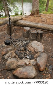 Bonfire site is made of logs and stones. The resting place is near river in taiga forest.