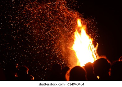 A bonfire with sparks with silhouettes of people against the background of the night sky