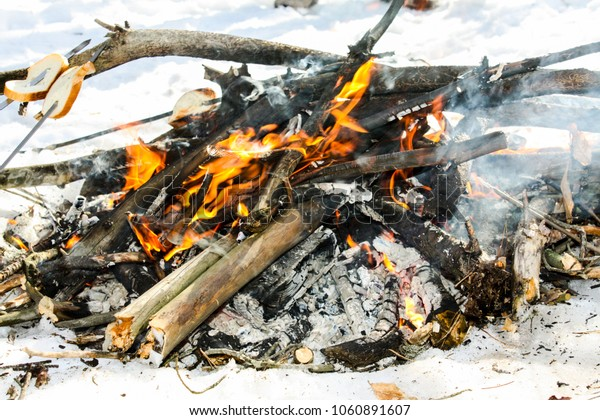 A bonfire in the winter forest. Hot bread on the fire.