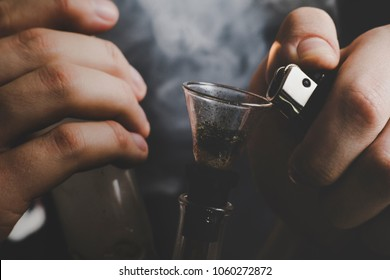 bong and a lighter in his hands. A man smokes cannabis weed, Smoke on a black background. Concepts of medical marijuana use and legalization of the cannabis. On a black background