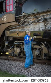 """BONGARDS, MN """" SEPTEMBER 8, 2018: Crew member does maintenance work on the steam engine Milwaukee Road #261 during a scheduled stop on its annual Autumn Tour from Minneapolis, MN to Glencoe, MN."""