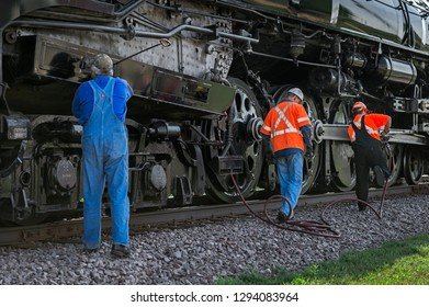 BONGARDS, MN – SEPTEMBER 8, 2018: Crew members do maintenance work on the steam engine Milwaukee Road #261 during a scheduled stop on its annual Autumn Tour from Minneapolis, MN to Glencoe, MN.