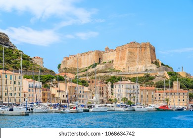 BONIFACIO PORT, CORSICA ISLAND - JUN 25, 2015: sailing yacht boats anchoring in Bonifacio port with citadel building in background. It is famous old town built on top of a cliff.