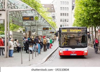 BONN, GERMANY - MAY 6, 2014: People waiting for the bus at bus stop in Friedensplatz