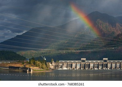 Bonneville Lock and Dam view in the Columbia River Gorge with rainbow and Eagle Creek after forest fire. Hydroelectric power generation structures between the USA states of Oregon and Washington.