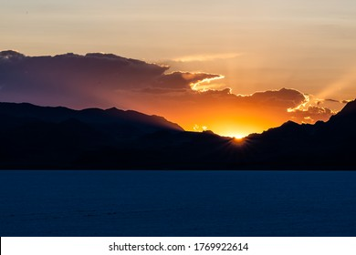 Bonneville Salt Flats dark blue landscape near Salt Lake City, Utah and silhouette mountain view and sunset sun rays glowing behind clouds