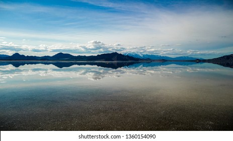 Bonneville Salt Flats located in Utah during Spring where a shallow layer or water creates a beautiful mirage of the sky and mountains in the background.