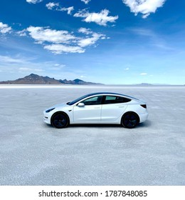 Bonneville Salt Flats, Utah / USA - July 31 st 2020 : Photograph of a white Tesla model 3 parked in salt flats in the US.