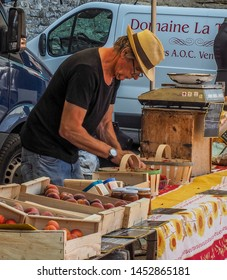 Bonnieux, France - June 28, 2019: Stall keepers selling their products at the French Market