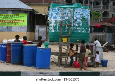 BONNY ISLAND, RIVERS STATE, NIGERIA, APRIL 15: Children collect water on April 15, 2006 at Bonny Island, Nigeria. Situated in the Niger Delta, the island hosts various major oil companies.