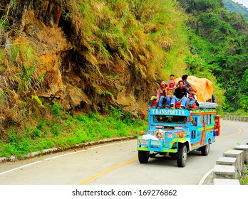 BONTOC, PHILIPPINES - MARCH 26, 2012: Passengers sit atop a very full jeepney The jeepney found everywhere in the country. It carries between 16 to 30 passengers.