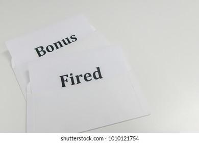 bonus and fired letter in envelope for business concept