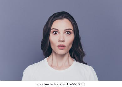 Boo! Portrait of attractive pretty charming stylish afraid brunette curly-haired girl in white t-shirt with staring big eyes, isolated over grey background