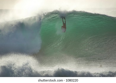 Boobie board rider catches a wave at Bonzai Pipeline off of Oahu's North Shore. (image contains noise)