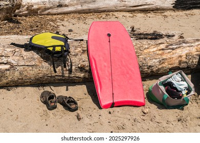 Boogie board, sandals, backpack and driftwood log on the beach at the ocean.