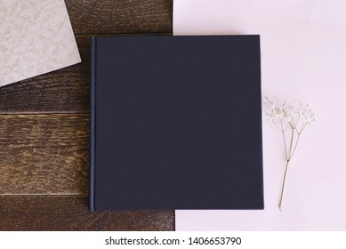 a book or an album with a black blank cover is lying on a wooden table, next to a pink sheet of paper and a sprig of flowers
