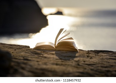 Book at the beach on a sea cliff with sunset in the background. Summer reading book on a vacation