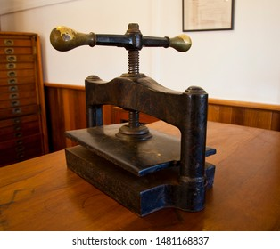 Book binding press. Antique iron vice with brass handles for clamping and squeezing during bookbinding handmade manufacturing process.