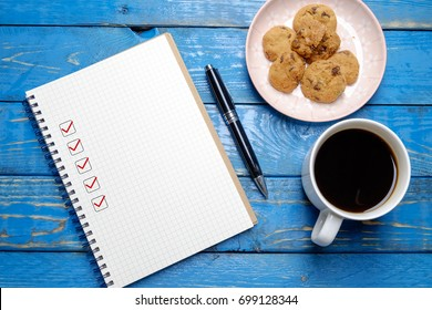 Book with blank checklist with coffee and cookies on blue wooden table