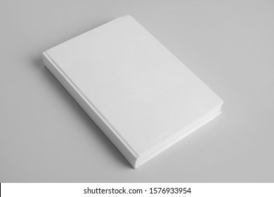 Book with blank cover on grey background
