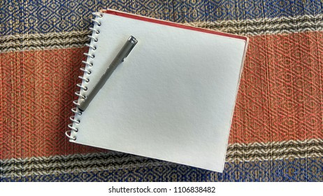 Book with a blank page and pen