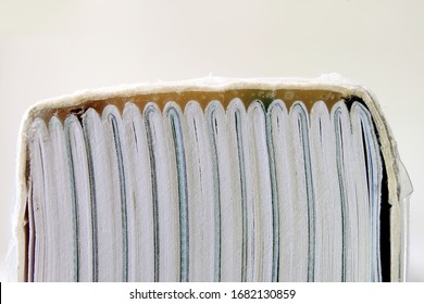 A book bound using perfect binding showing the spine and glue holding folded sections of the book together. Pages of a book glued together with the cover using a strong adhesive. Closeup macro view.