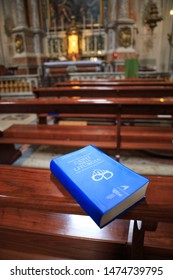 Book of chants for the liturgy - Diocese of Bologna, Italy. In blue cover, laying unopened on a pew. Jul 15.2019.
