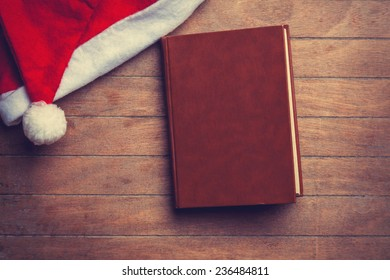 Book and christmas hat on wooden table.
