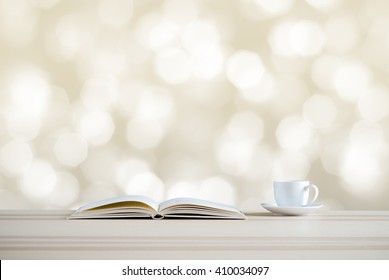 book and coffee cup on bokeh background