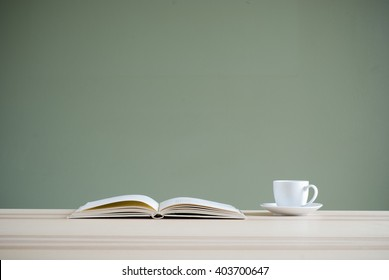 book and coffee cup on desk