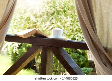 Book and coffee in the garden terrace - peaceful weekend morning concept
