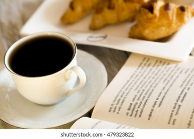 Book and croissants with coffee on the wooden table