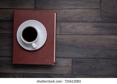 Book, cup black tea or coffee, top view on wooden background, desk.