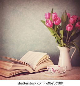 Book, a cup of tea and pink tulips in a vase