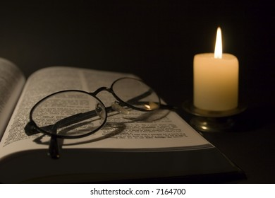 A Book and Eyeglasses under the Candlelight