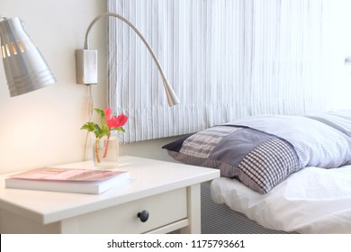 A book and flowers on a nightstand table in the bedroom on a sunny morning